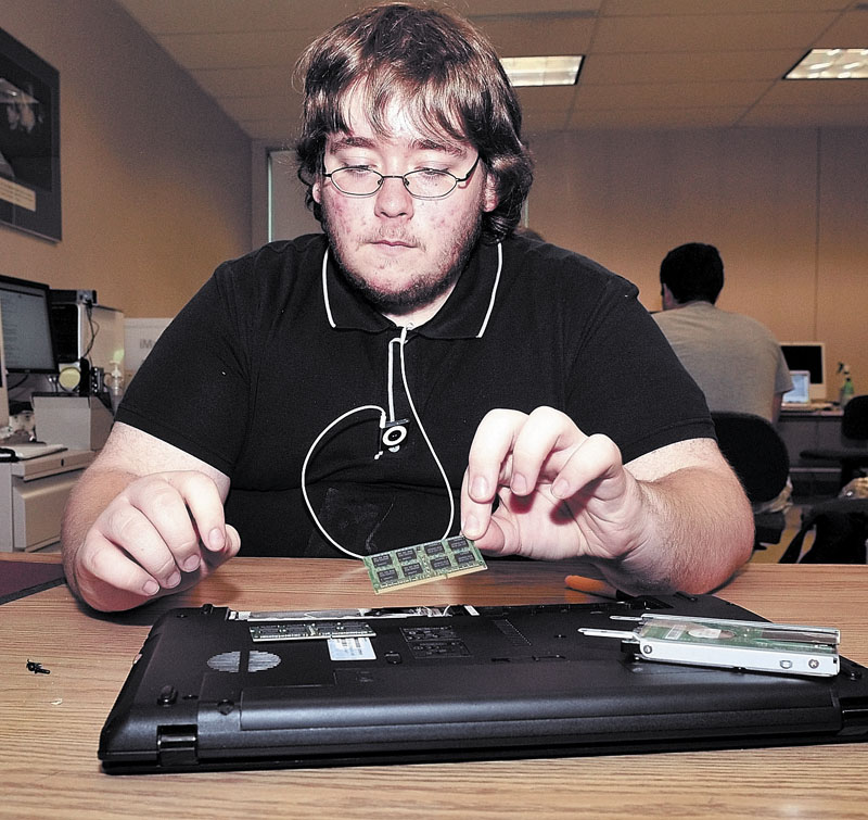HIGH-TECH: Andrew Leonard of Waterville removes the hard drive and other components of a computer during a program at the University of Maine at Farmington. Students are getting a chance to take classes, work part-time jobs and stay on a college campus as part of the Upward Bound summer program.