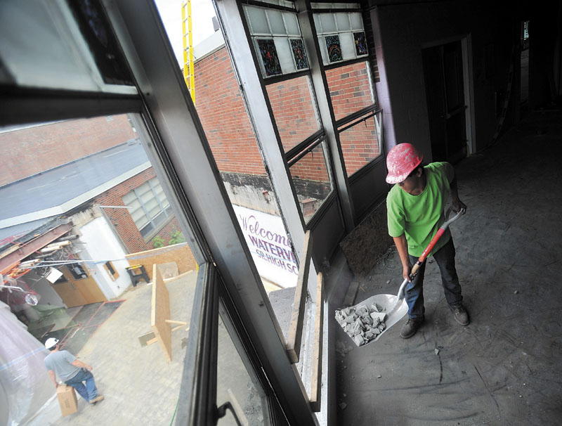 WORKING: Taddy Bibeault, 18, a laborer with SMS Demolition, clears refuse from the second story of Waterville Senior High School during renovations on Friday. Workers are finishing the second week of the three-week phase of remodeling the school.