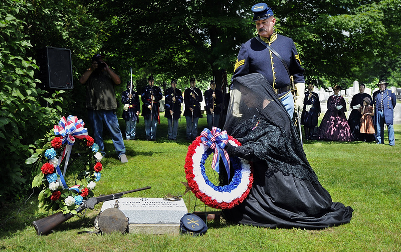 Carolyn Lawson, a member of the Auxillary of the Union Veterans of the Civil War, lays a wreath at the new headstone of the grave of Private William Johnson, a Union soldier in the Civil War, with the assistance of Mike Nugent of the 1st Cavalry reenactors during a special ceremony today marking the newly confirmed grave of Civil War Private William Johnson at Baptist Cemetery, Yarmouth. In back are the 3rd Maine Infantry reenactors and related character reenactos of the Civil War era.
