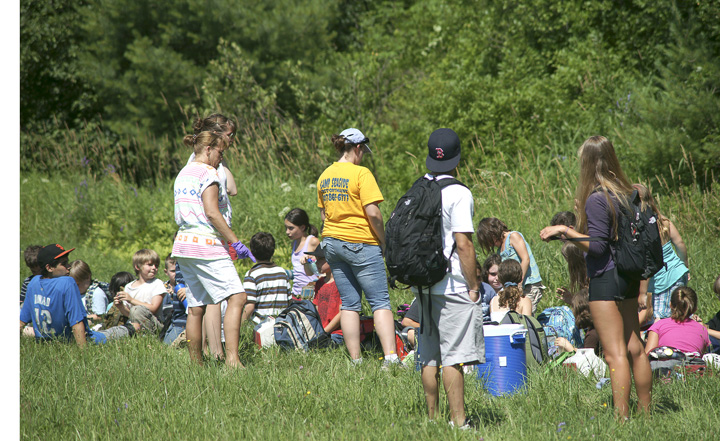 School bus passengers wait in the grass after the accident on I-295. The RSU 5 bus was carrying 30 children and six staff members who were returning from a field trip in Portland.