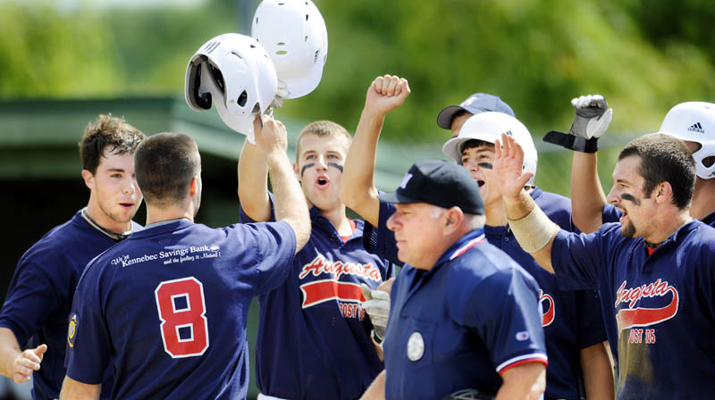 RALLY: Augusta's Corey Lapierre celebrates with teammates at home plate after hitting a home run against Brewer during the American Legion baseball state tournament Wednesday in Augusta. Augusta beat Brewer 16-4 in a game shortened to seven innings by the 10-run rule.