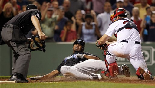 Toronto Blue Jays' Edwin Encarnacion, center, slides into home plate as Boston Red Sox catcher Jason Varitek, right, prepares to tag him out in the ninth inning Tuesday at Fenway Park, in Boston. Encarnacion was called out, ending the game and giving the Sox a 3-2 win.