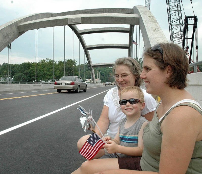 Zachary Niederfringer, 4, waves a flag and pinwheel at cars passing for the first time over the new bridge that spans the Kennebec River on Thursday in Norridgewock. He sat with his mother, Rebecca, and grandmother, Janice Malek, who lives next to the bridge. Zachary said he can't wait to ride his bike across to the other side.