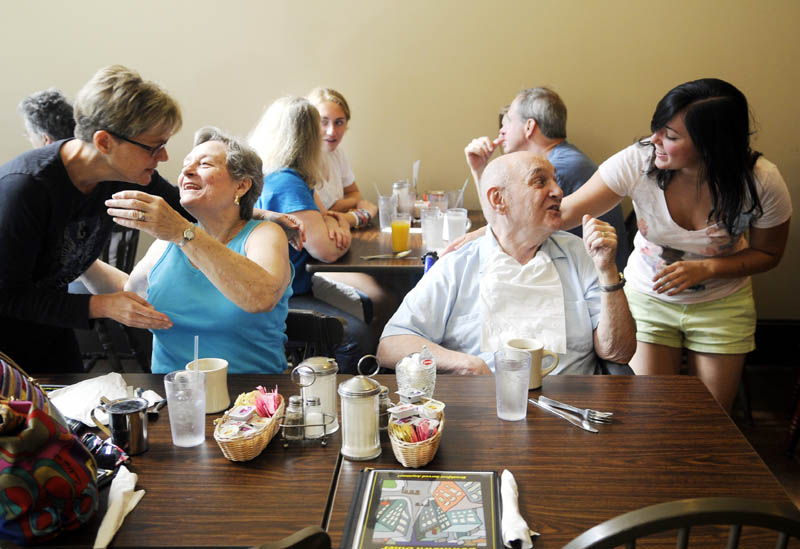 Rachael Stetson, right, greets her grandfather, James Welton, as her mother, left, MaryBeth Welton, hugs his wife, Elzabeth Welton, Monday at the Downtown Diner in Augusta. The recently opened cafe is attracted large number of diners, according to the proprietors.