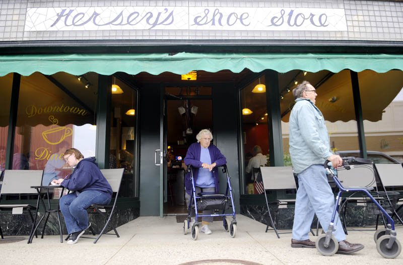 Customers exit the Downtown Diner on Water Street in Augusta, which features tables and chairs on the sidewalk.