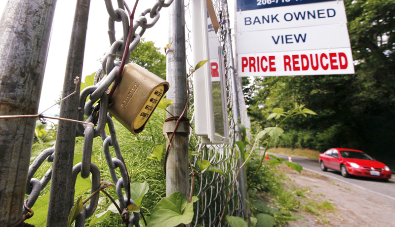 "A ""bank-owned"" lot is chained and locked but advertised for sale in Seattle in this June 9 photo."