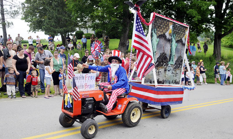 OUT IN FRONT: A lawnmower towing a trailer leads the Fourth of July parade Monday through Kings Mills in Whitefield. The annual celebration draws hundreds to watch and participate in the pageantry and patriotism.