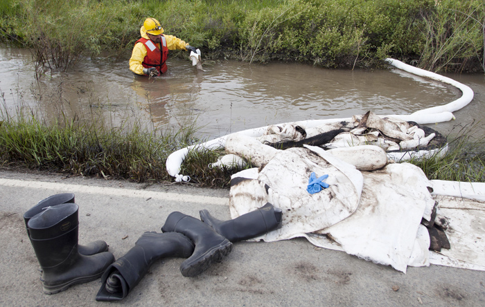 Cleanup crews work to collect oil from along side the Yellowstone River in Laurel, Mont., Monday.