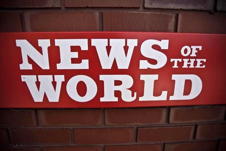 News of the World sign is seen by an entrance at premises of News International in London. James Murdoch, News Corporation executive says the News of the World will publish its last issue on Sunday. The focus of the phone hacking scandal shifted today to serious allegations of police corruption as Scotland Yard called for an independent review of reported payoffs by journalists to police.