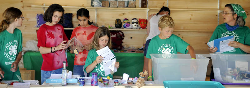 COME ONE, COME ALL: Members of Bluebird 4-H Club, of Benton, set up items for display Tuesday in the new Exhibition Hall at the Pittston Fair. The annual agricultural fair starts Thursday and ends Sunday.