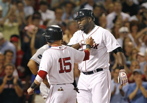 Boston Red Sox designated hitter David Ortiz is congratulated by Dustin Pedroia (15) after hitting a grand slam against the Kansas City Royals in the fourth inning Wednesday at Fenway Park in Boston.