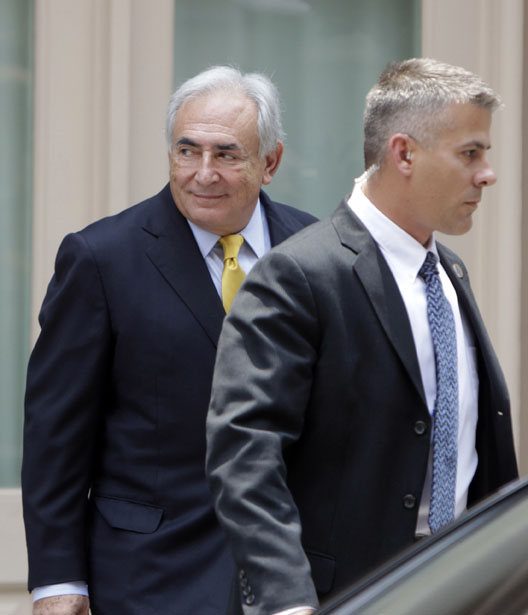 Former IMF head Dominique Strauss-Kahn, left, leaves his rented house escorted by security today in New York.