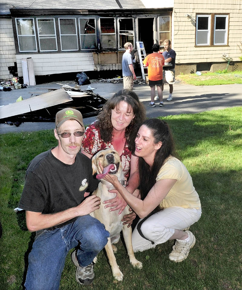 Neighbors Randy LaPointe, Betsy Abbott and Debra Kilsby crowd around dog Abby Doodle, who they rescued last Saturday after fire erupted on the porch of a home in Waterville. People for the Ethical Treatment of Animals is giving the three rescuers its Compassionate Action Award. In background, homeowners Chris and Heather Stone speak with contractor Sheldon Skidgel, right.