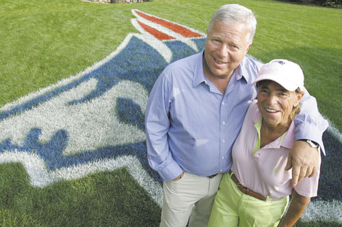 In this June 22, 2005, file photo, PERFECT PAIR: New England Patriots owner Robert Kraft and his wife Myra pose in front of a Patriots logo painted on their lawn in Brookline, Mass., in 2005. Myra Kraft died Wednesday after a battle with cancer.