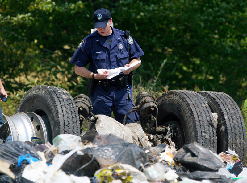 ACCESSING THE DAMAGE: A Maine state police officer inspects the remnants of a tractor-trailer that collided Monday with an Amtrak passenger train in North Berwick.