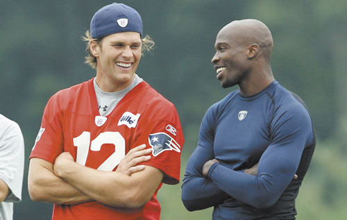 WELCOME: Tom Brady, left, and Chad Ochocinco share a laugh during a training camp session Friday at Gillette Stadium in Foxborough, Mass. Ochocinco was traded to the Patriots on Thursday from the Cincinnati Bengals, according to a source, but the deal has yet to be announced and Ochocinco cannot yet practice.
