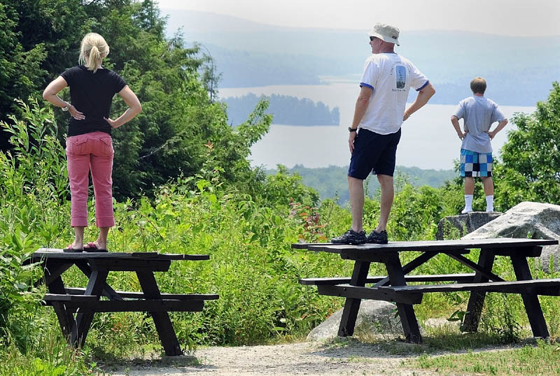 Jen Porter, left, and Mike Riley and Jack Hubley take in the views of the Belgrade Lakes through the haze from high atop Blueberry Hill this week in Rome. Temperatures are again likely to near 100 today, but Sunday should offer a reprieve.