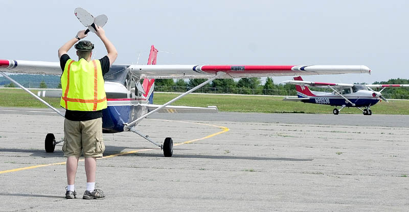 Civil Air Patrol cadet Avery Spear directs a plane's crew into position on Tuesday at the Augusta State Airport.