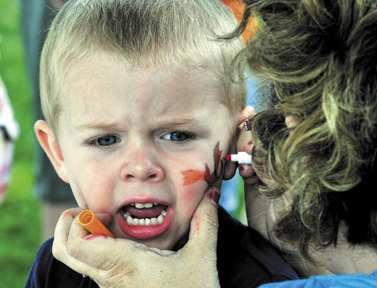 Staff photo by David Leaming ROAR: Mack Merrow looks a little nervous as Bobbi Estes paints a dragon on his face during the Central Maine Egg Festival Egglypics games at Hathorn Park in Pittsfield on Wednesday.