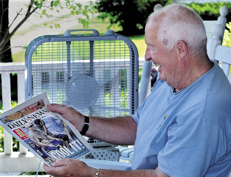 NO FAN OF HEAT: Walter Frame cools off with an electric fan blowing while reading the New York Daily News on his porch in Waterville on a hot and muggy Friday. Not surprisingly, the metro newspaper ran a photo of two men also cooling off with a fan as hot weather scorches the East Coast. More heat is expected today.
