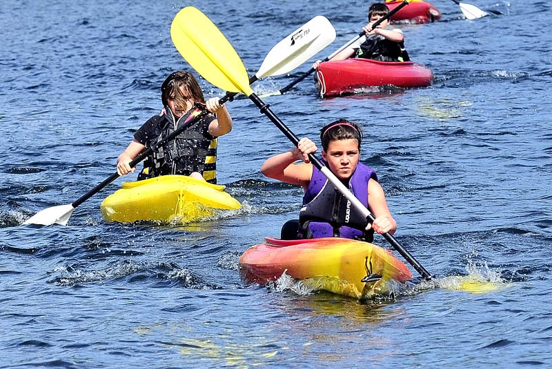 During Camp Loon Survivor Island events on Friday, Katie Guarino leads Elizabeth Newman and Nick Veilleux in a kayak race on Great Pond beside the Belgrade Community Center for All Seasons.