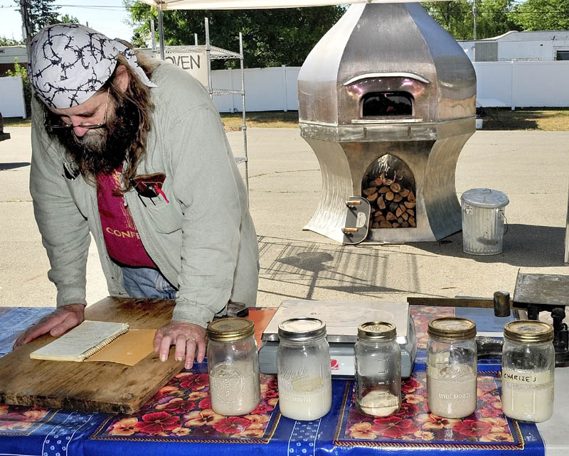 Dusty Dowse goes over notes while preparing his talk and demonstration on baking sourdough breads in a wood-fire oven during the Kneading Conference in Skowhegan on Thursday.