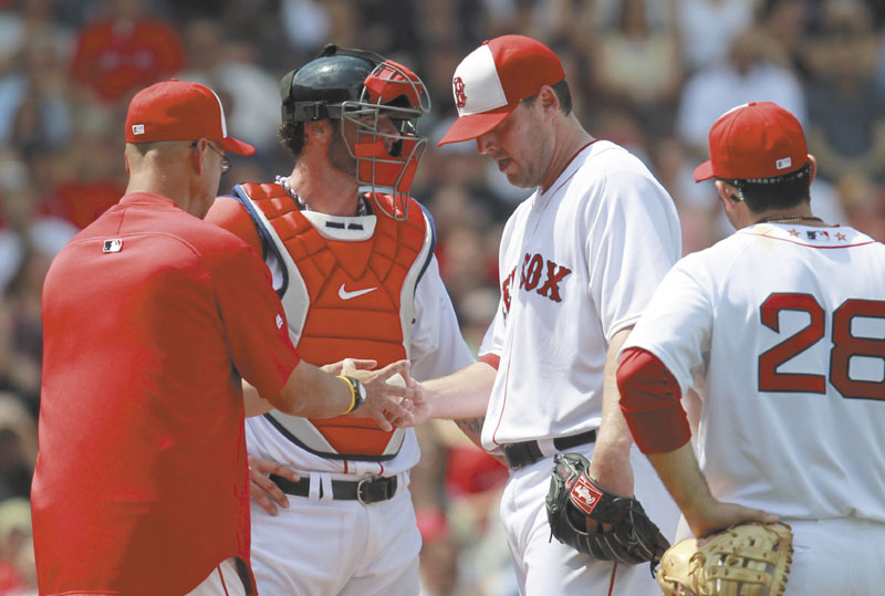 FEELING DOWN: Boston Red Sox pitcher John Lackey, center, once led the American League with a 3.01 ERA in 2007. This season, his ERA is 7.47 and he has allowed 70 base runners in 34 1/3 innings at Fenway Park this season.