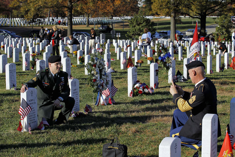 HONORING OTHERS: Command Sgt. Maj. Jeff Mellinger, right, photographs Sgt. Timothy Weichert, from Rockville, Md., next to the grave of Robin Towns Sr., on Veterans Days last year in Section 60 of Arlington National Cemetery in Virginia. Set to retire this summer, Mellinger, 58, the last Vietnam-era draftee, said he personally knows about 40-50 people buried at Arlington. He visits with families of the fallen at the cemetery and with wounded troops at Walter Reed Army Medical Center most weekends he's in town.