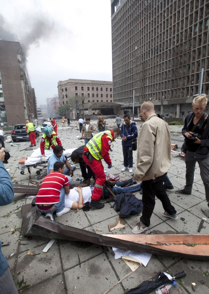 BLOODY ATTACK: People are treated at the scene after a Friday explosion in Oslo, Norway. Police linked one Norwegian to both attacks, which killed a total of at least 16 people in nation's worst violence since World War II. BNC