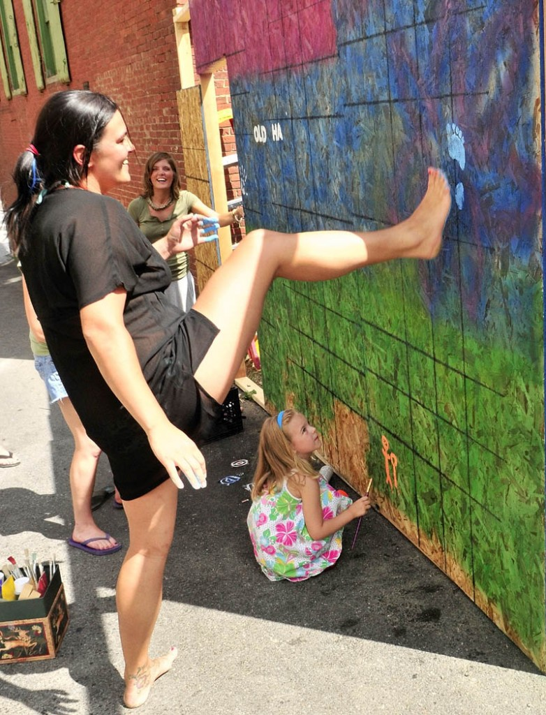 FANCY FOOTWORK: Madison Boynton, bottom, watches as Deanna Thibeau pulls her leg back after making a blue-painted footprint on a plywood mural wall Wednesday in Dummers Lane. The mural on the temporary plywood wall in the alley between the Liberal Cup and Higher Grounds will be part of the Old Hallowell Day beer garden at Higher Grounds.