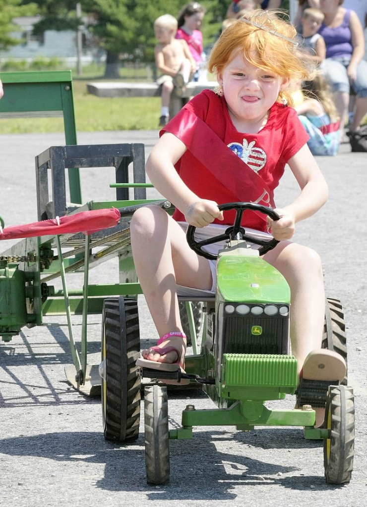 Caleigh Crocker, 5 of Windsor, strains to pedal in the kiddie tractor pull contest on Saturday morning at the Pittston Fair. The fair runs through this afternoon and is located on Route 194 near Mast Road.