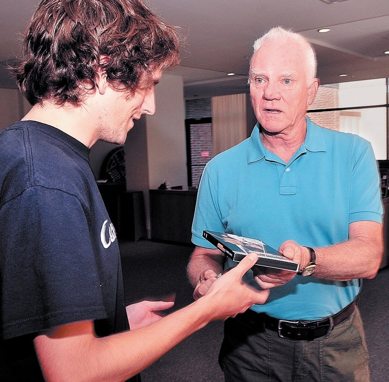 """AUTOGRAPH: Actor Malcolm McDowell, right, signs a copy of """"A Clockwork Orange"""" for Chris Harmon after a discussion of his career on Saturday at a Maine International Film Festival event at Colby College in Waterville."""