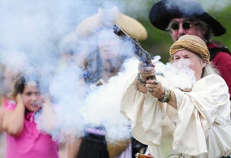 A young spectator covers her ears as cannons and guns fire during a pirate battle on Saturday during Richmond Days events at Fort Richmond Waterfront Park.