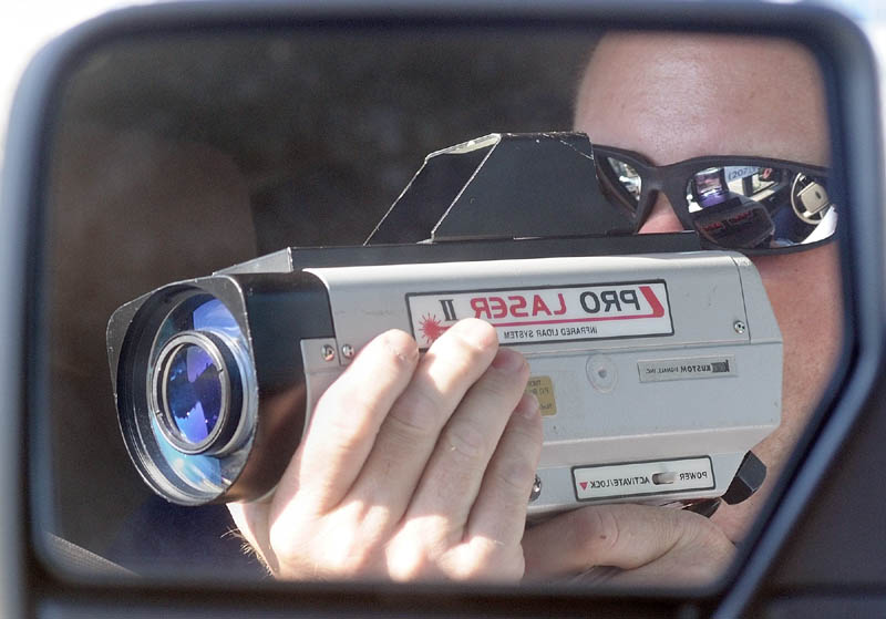 Sgt. Christopher Shaw is reflected in the mirror of an unmarked sport utility vehicle while he points a laser gun to clock the speed of oncoming during a speeding enforcement detail Friday morning on Western Avenue in Augusta. When he spotted a speeder he dispatched one of four officers after the car.
