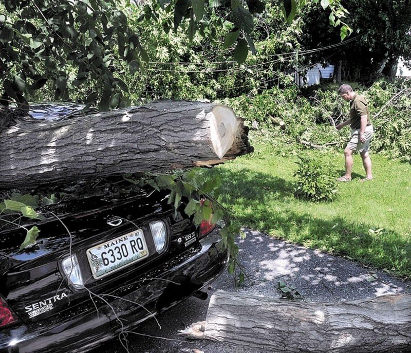 THE STORM'S AFTERMATH: Apartment owner Derik Saucier on Thursday walks past fallen power lines and trees that cover and damaged his building and a neighbor's vehicle during a violent storm Wednesday night on School Street in Waterville.