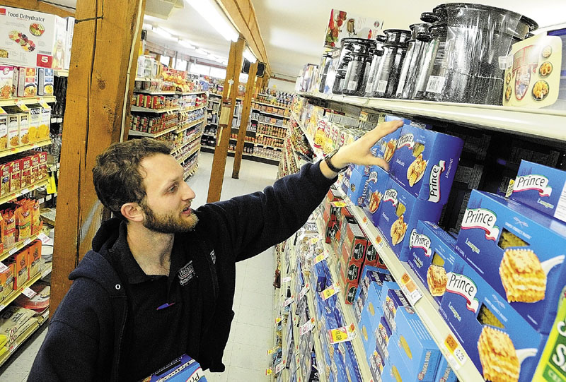 WORKING: Jonathan Pelton stocks shelves on Wednesday afternoon at Hussey's General Store in Windsor. Pelton, of South China, is working there on summer break from college and has been employed there since high school.