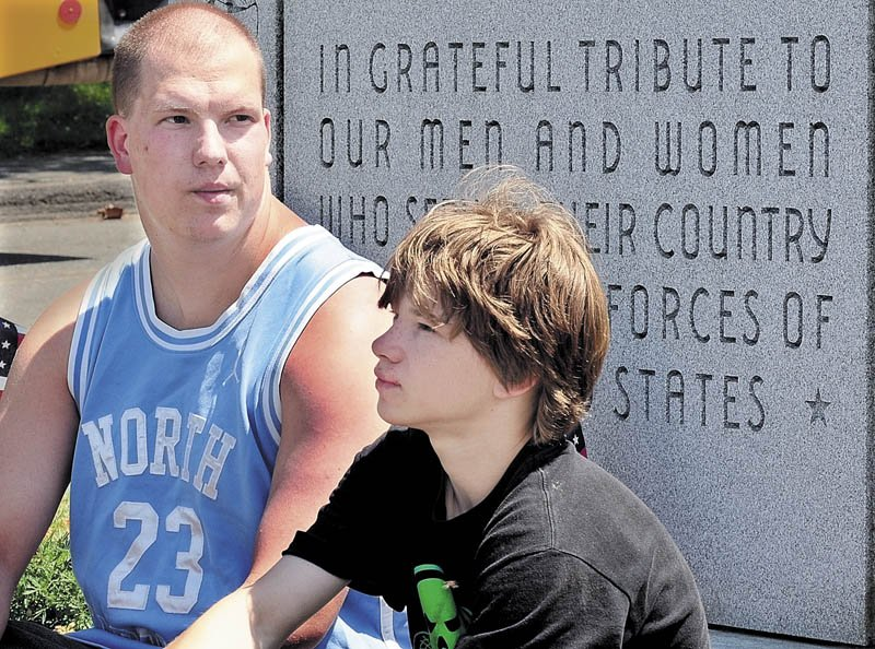 FAMILY AND FRIENDS: Justin Bennett and Zachary Martin, right, remember Tyler Springmann on Tuesday at a veterans monument in Hartland. Springmann, Zachary's brother, was killed Sunday while serving in the U.S. Army in Afghanistan.