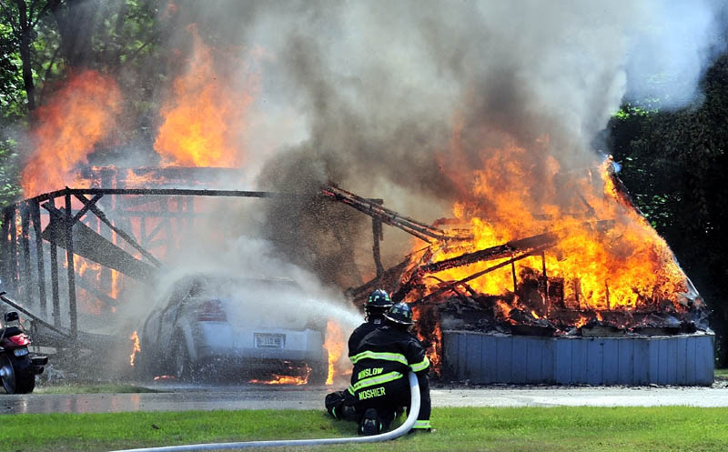ALL GONE: Winslow firefighters spray water that engulfed a mobile home and vehicle owned by Priscilla Ouellette, 64, on Friday at the Pleasant Ridge Mobile Home Park in Winslow. Ouellette grabbed her dog, Mackey, and escaped without injury.