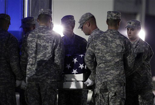 KILLED IN AFGHANISTAN: An Army carry team carries the transfer case containing the remains of Army Spc. Mark J. Downer of Warner Robins, Ga., upon arrival at Dover Air Force Base, Del., on Saturday.