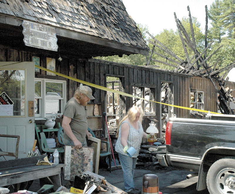 DAMAGE: Rick and Lynn Doane remove what they can on Monday from Pick & Paws Collectibles on U.S> Route 2 in Mercer after fire destroyed the building Saturday night.
