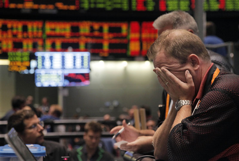 OUCH: Trader Andrew Stavros reacts after the close of trading on the floor of the CME Group on Monday in Chicago. Stocks plunged worldwide Monday on a host of concerns, including Friday's downgrade of the U.S. government's credit rating by Standard & Poor's.