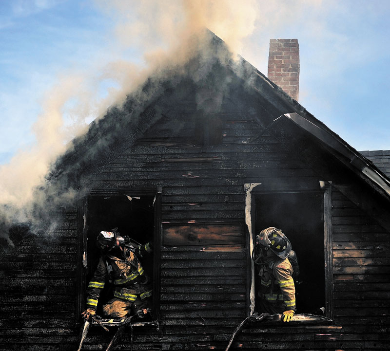 DESTROYED: Firefighters are seen in the charred windows of a house on Oak Street in Waterville Tuesday morning. A family of four was left homeless by the blaze.