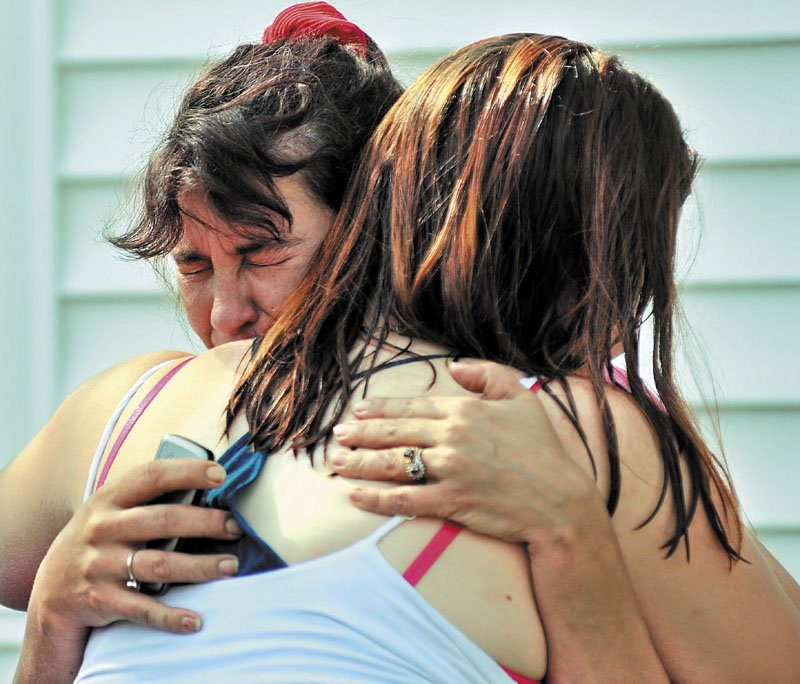 EMBRACE: Tracey Bragdon, left, owner of the Oak Street home destroyed by fire Tuesday morning in Waterville, is consoled by a friend as firefighters battle the blaze.