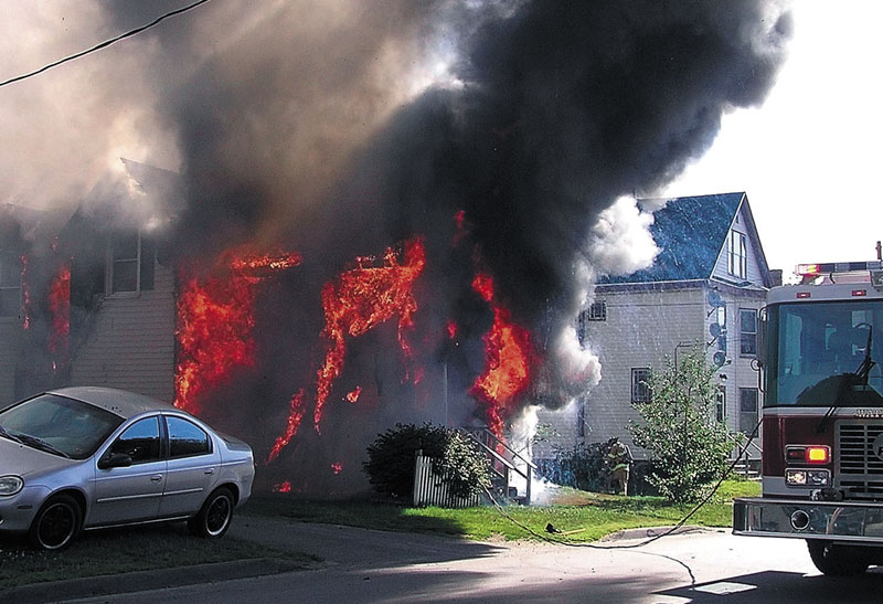 ON FIRE: A house on Oak Street in Waterville is consumed by flames Tuesday morning as firefighters arrive on the scene.