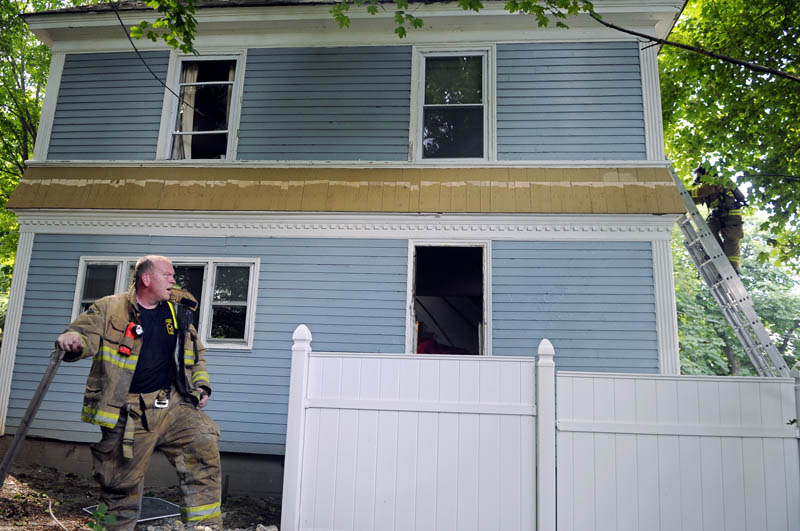 BEAT THE HEAT: Augusta firefighter Greg Coniff, left, catches his breath Tuesday as a colleague ascends a ladder into an Augusta home that caught fire. Firefighters were able to extinguish the blaze quickly.