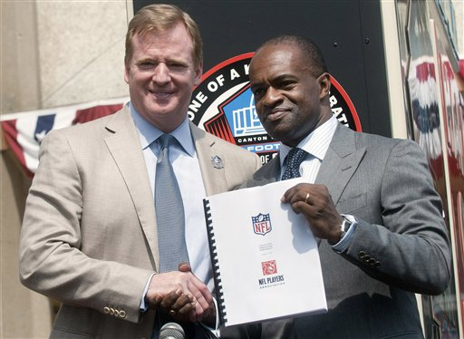 NFL Comissioner Roger Goodell, left, and NFLPA Executive Director DeMaurice Smith, shake hands after signing their collective bargaining agreement Friday at the Pro Football Hall of Fame in Canton, Ohio.
