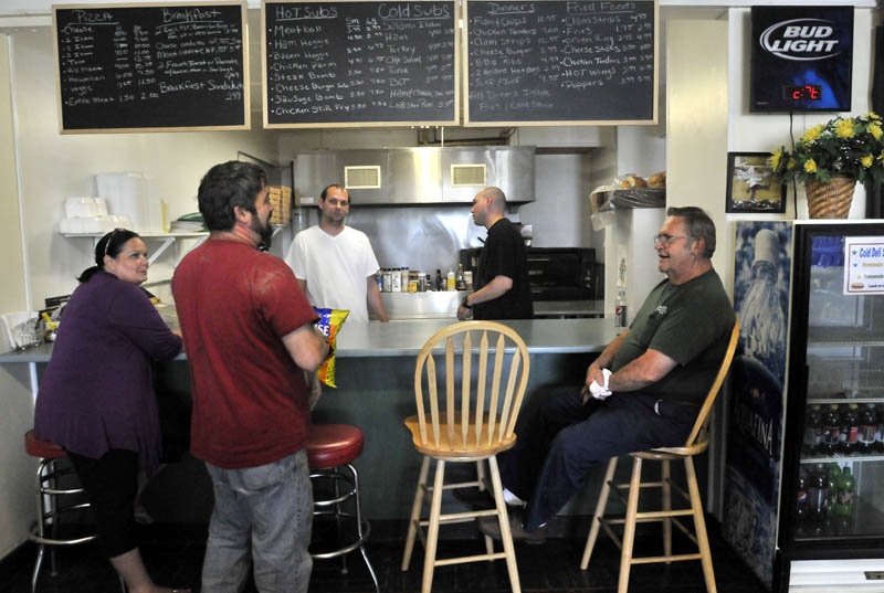 Brenda DiMeo, far left, and her sons Jeremy, back center in white shirt, and Tony, back center, owners of the Cambridge General Store in Cambridge share a luagh with local customers on Friday. Cambridge General Store is the only retail outlet in Cambridge.