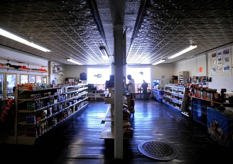 Jeremy DiMeo, center, stocks the shelves of his family's store, Cambridge General Store on Main Street in Cambridge Friday.