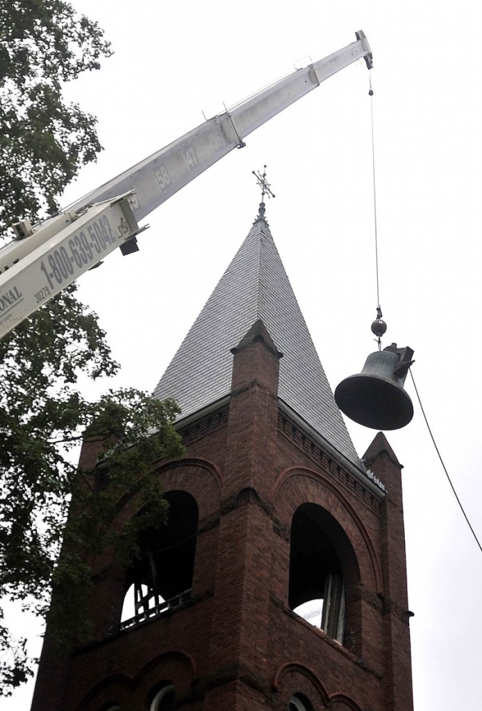 A crane from MMR Professional Steeplejacks, hoist the 100-year-old Meneely bell from the belfry of the Old South Congregational Church on Main Street in Farmington Wednesday morning.
