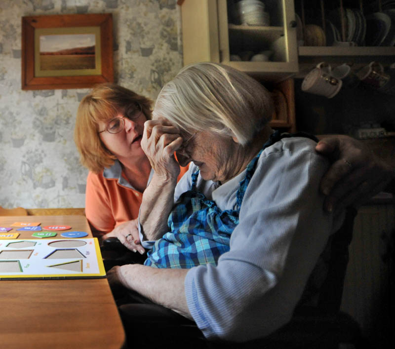 Cheryl Barkow, back, comforts her mother, Alice Osborne, 93, as she tries to complete a puzzle at the kitchen table at Barkow's New Sharon residence recently. Barkow and her husband Larry care for Cheryl's mother, who has dementia.